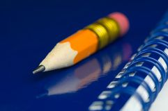 Short pencil. Short orange pencil in closeup on a blue notepad Stock Image