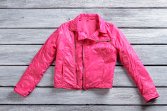 Short pink jacket. Pink jacket on wooden background. Stylish outerwear for girls. Garment made of synthetic fabric Royalty Free Stock Images
