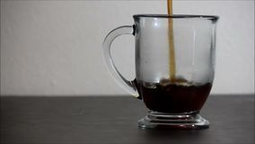 Simple shot of coffee added to mug on dark table. A short pour of coffee into a clear coffee mug. Mug placed on clean table against white wall