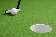Short putt. Putter about to tap ball into hole Royalty Free Stock Photography
