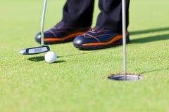 Short Putt. Golf green hole course man putting ball inside short putt Stock Photos