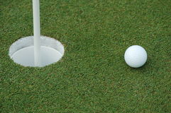 Short Putt. A white golf ball sitting next to the hole with pin inserted. A tap in Royalty Free Stock Photo