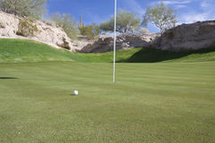 Short Putt Coming Up. A golf ball close to the flag on a golf green in the arizona desert Stock Photos