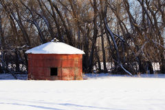 A short, red grain bin. A short, round, red grain bin in front of a line of trees in the winter Royalty Free Stock Photo