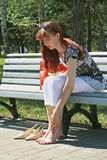 Short rest for legs. The young woman sits on a bench barefooted Stock Photo