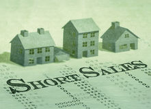 Short sales. Wording on past dues bills. Blurred house models background Royalty Free Stock Photos