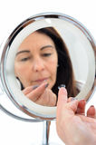 Short sighted middle aged woman. Short sighted 50-year-old woman with contact lens balanced on the end of her finger in front of mirror Stock Images