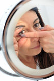 Short sighted woman puts a contact lens. Short sighted 50-year-old woman puts a contact lens in front of mirror Stock Images