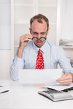 Short sighted at work - balding businessman looking through glas Stock Image
