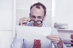 Short sighted at work - balding businessman looking through glas Stock Images