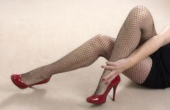Short skirt, fishnet tights and red high heels. Portrait of a mature woman wearing black fishnet tights and red shoes Stock Photography