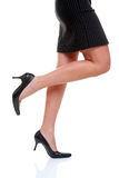 Short skirt long legs and high heels. Womans legs wearing a short pinstripe skirt and black high heel shoes, on a white background Royalty Free Stock Photo