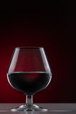 Short-stemmed glass on a dark background. Red wine in a short-stemmed glass on a dark background Stock Image