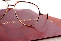 Short Stories. A leather cover book of short stories & reading glasses with metallic frame on them stock photo