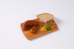 Short thick sausages with bread. Short thick sausages with slices of bread and mustard on wooden cutting board stock images