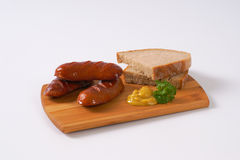 Short thick sausages with bread. Short thick sausages with slices of bread and mustard on wooden cutting board royalty free stock image