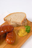 Short thick sausages with bread. Short thick sausages with slices of bread and mustard on wooden cutting board royalty free stock images