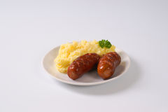 Short thick sausages with mashed potatoes. Roasted short thick sausages with mashed potato puree on white plate stock photography