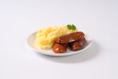 Short thick sausages with mashed potatoes. Roasted short thick sausages with mashed potato puree on white plate royalty free stock photography