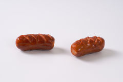Short thick sausages. Roasted short thick sausages on white background royalty free stock image