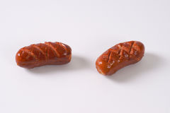 Short thick sausages. Roasted short thick sausages on white background stock photography