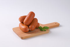 Short thick sausages. On wooden cutting board royalty free stock images