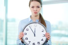 Short of time. Conceptual portrait of a business lady with clock being short of time Royalty Free Stock Images