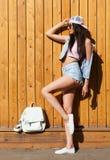 Short vestindo das calças de brim da menina do moderno, revestimento com a trouxa que levanta contra a parede de madeira da rua,  imagem de stock