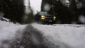Van Drives By Splashing Snow Frozen Icy Road Winter Conditions. Short video of a van driving in slushy winter road conditions cloudy skies stock video footage