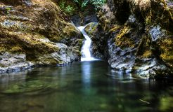 Short waterfall slides into a pool of smooth water with black mossy rocks on the lower Rogue River in Oregon. Short waterfall slides into a small pool of smooth stock image
