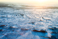 Short winter day in tundra, top view. Aerial view above the endless snow covered tundra in time of short winter day. Small polar trees are illuminated by the low Royalty Free Stock Photos