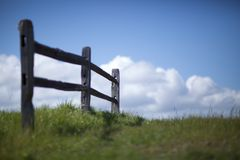 Small Fence. A short wooden fence in a meadow with blue sky, clouds, and green grass Stock Photo