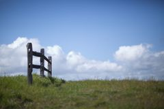 Small Fence 02. A short wooden fence in a meadow with blue sky, clouds, and green grass Stock Image