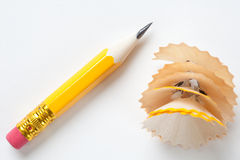 Short yellow pencil on textured white paper. Very short yellow pencil with shavings on textured white paper Royalty Free Stock Images