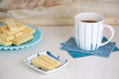 Shortbread biscuits and tea. Delicious homemade shortbread biscuits on a couple of blue plates and a cup of tea for afternoon tea Stock Images