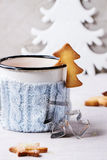 Shortbread Christmas cookies for cups. Vintage cup of hot tea in knitted cup holder, cinnamon sticks and sugar powder over table with white tablecloth with Royalty Free Stock Images