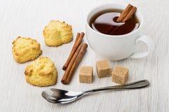 Shortbread ciastka, cukier, cynamonowi kije, teaspoon, filiżanka herbata obraz stock