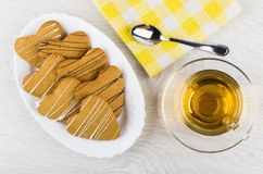 Shortbread cookies in form heart in dish, napkin, tea, teaspoon. Shortbread cookies in form heart in dish, napkin, cup of tea, teaspoon on wooden table. Top view Stock Photo