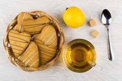 Shortbread cookies in form heart, lemon, sugar, tea and teaspoon. Shortbread cookies in form heart in wicker basket, lemon, sugar, tea and teaspoon on wooden Stock Photos