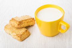 Shortbread cookies with sesame and cup of milk on table Stock Images