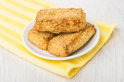 Shortbread cookies with sesame in saucer on yellow napkin Royalty Free Stock Images