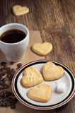 Shortbread cookies in shape of heart and coffee. Shortbread cookies in shape of heart in plate and cup of coffee on old wooden table royalty free stock images