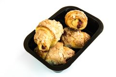 Shortbread cookies in a take-away package. Shortbread baked croissants sprinkled with sugar and filled with fruit filling, arranged in a take-away package Stock Photos