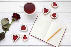 Shortbread heart shaped cookies with empty notebook, pencil, cup of tea and rose flower on white wooden background for Royalty Free Stock Photo