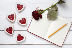 Shortbread heart shaped cookies with empty notebook, pencil and rose flower on white wooden background for Valentines Stock Photo
