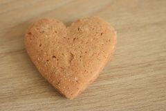Shortbread heart on wooden background in warm light as love background. Shortbread heart on grey wooden background in warm light and colors as love background Stock Photo