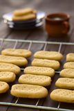 Shortbread. Homebaked shortbread biscuits on cooling rack with plates and cup of tea in the back (Selective Focus, Focus on the front of the second cookie in the Royalty Free Stock Images