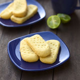 Shortbread. Homebaked shortbread biscuits on small plates with cup of tea in the back (Selective Focus, Focus on the front of the upper shortbread Stock Photos