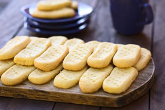 Shortbread. Homebaked shortbread biscuits on wooden board with plates and cup of tea in the back (Selective Focus, Focus on the front of the upper cookies Stock Photos