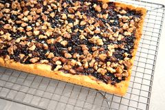 Shortbread pie with jam and walnuts on cooling rack stock photo